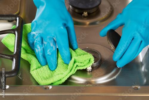 Leinwandbild Motiv Gloved hands removing soap from stove top range with microfiber