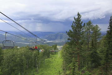 Tourists at the ski lift on a background of thunderclouds in the