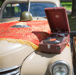 Car cowl GAZ-M-20 Pobeda, old player and flag on show Retro cars