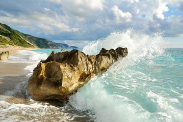 Big sea wave breaking on the beach rocks with a high sea spray