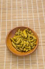 turmeric (Curcuma longa) dry roots in wooden plate
