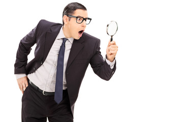 Shocked businessman looking through a magnifier