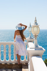 girl in white dress and hat looking at the sea