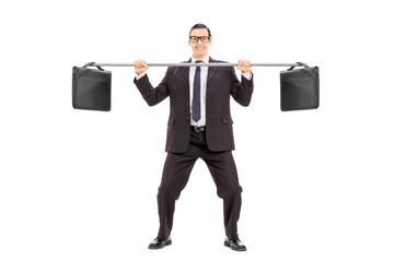Businessman balancing two briefcases on a pipe