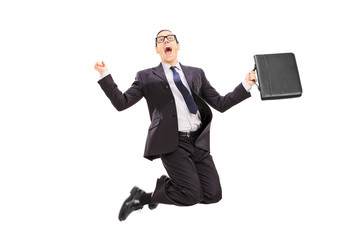 Businessman with briefcase jumping out of joy