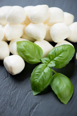 Green basil and mini mozzarella balls, close-up, vertical shot
