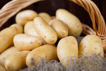 Close-up of raw potato in a wicker basket, horizontal shot