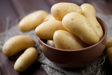 Raw potato over wooden background, horizontal shot