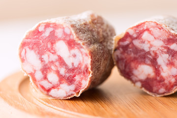 Salami on wooden board close up