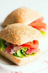 Prosciutto sandwiches with tomato and arugula on table