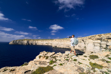 Man taking picture of coastline near Azure Window on Gozo Island