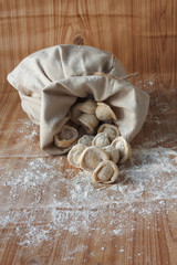 hand-made pelmeni in linen bag on a wooden background