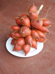 Fresh salacca edulis salak palm fruit in dish.