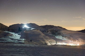 Mountain scene with ski slopes at night.