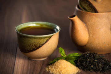 Teapot, cup of black tea with mint leaves and brown sugar