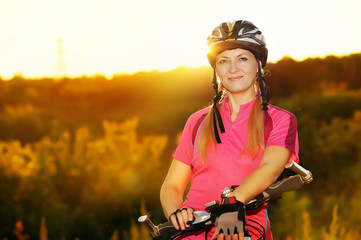 cycling woman on sunset background