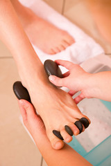 Woman receiving hot stone massage feet