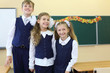 Two girls and boy in uniform stand in classroom and smile