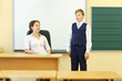 Teacher sits at table and looks at boy answering near blackboard