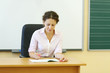 Young teacher in white shirt checks exercise book at desk