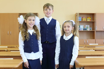 Two happy girls and boy in uniform stand in classroom at school.