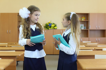 Two happy girls in uniform stand in classroom with exercise book