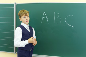 Boy stands near green chalkboard with ABC in classroom