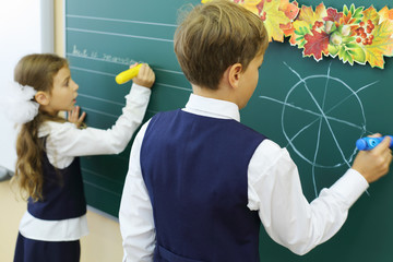 Back of boy drawing and girl writes on chalkboard in classroom