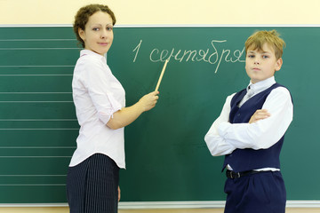 Boy and teacher stand near green chalkboard