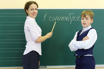 Boy and teacher with pointer stand near chalkboard