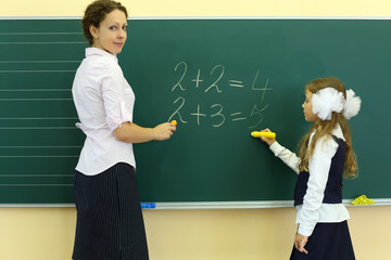 Girl and teacher stand near chalkboard