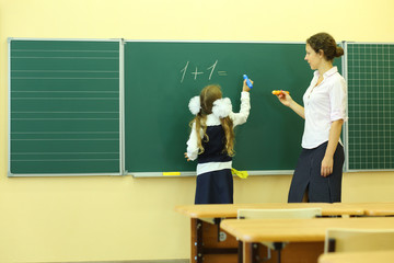 Girl and teacher near chalkboard solve simple math examples
