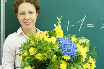 Happy teacher with big bunch of flowers stands near chalkboard