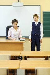 Teacher sits at table and checks exercise book and boy looks