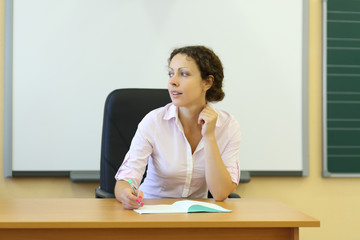 Young teacher in white shirt sits at table with exercise book