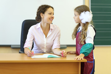 Teacher sits at table with exercise book and looks at girl