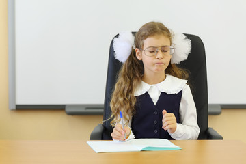 Girl in glasses sits at teacher table with exercise book