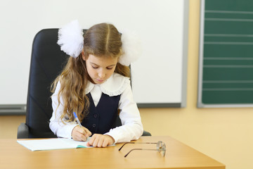 Girl in vest sits at teacher table and writes in exercise book