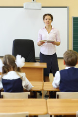 Teacher talks near chalkboard and pupils listen her at desks