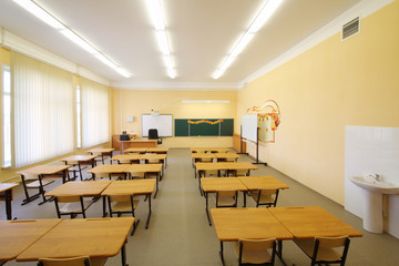 Empty classroom with wooden desks, chalk board and yellow walls