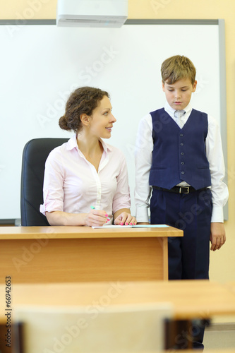 Smiling teacher checks exercise book and boy looks at her