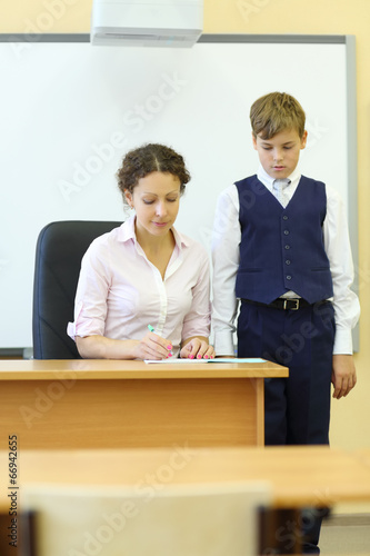 Teacher grades in exercise book and boy looks at it in classroom