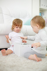Two little girls sit on carpet and play with white box.