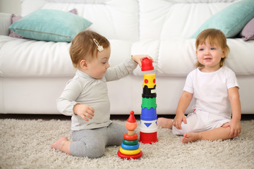 Two pretty kids sit on carpet and play with toys near sofa