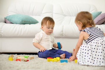 Two barefoot kids sit on carpet and play with wooden cubes