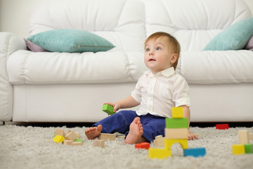 Barefoot baby sits on carpet with wooden cubes and looks up