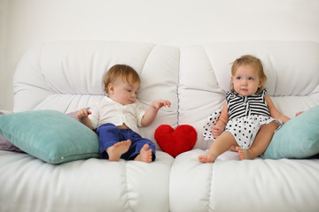 Two barefoot kids sit on white sofa with pillow