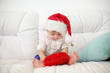 Cute little kid in red cap sits on white couch with red pillow