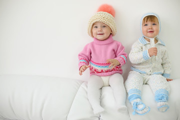 Two little kids in hats and knitted jackets sit