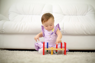 Little girl in dress plays with toys near white sofa at home